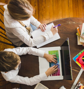 Kids working together from dinner table while they stay at home