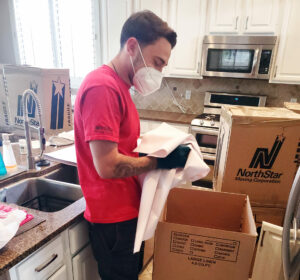Mover wearing protective COVID-19 Gear while packing