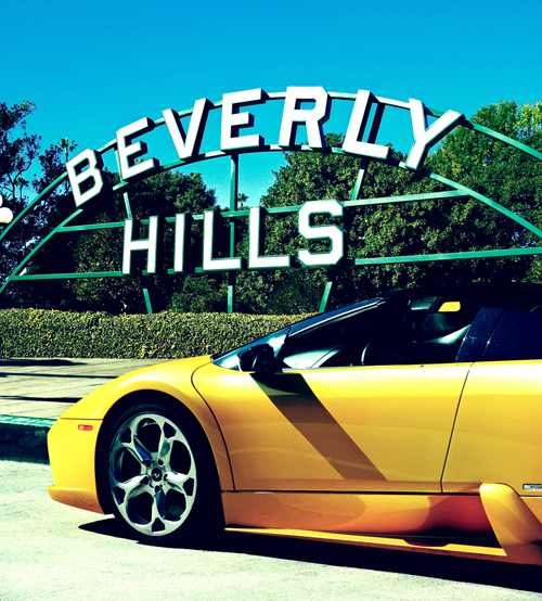 A Lamborghini in front of the Beverly Hills sign