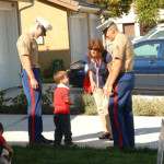 Military members talk to a child